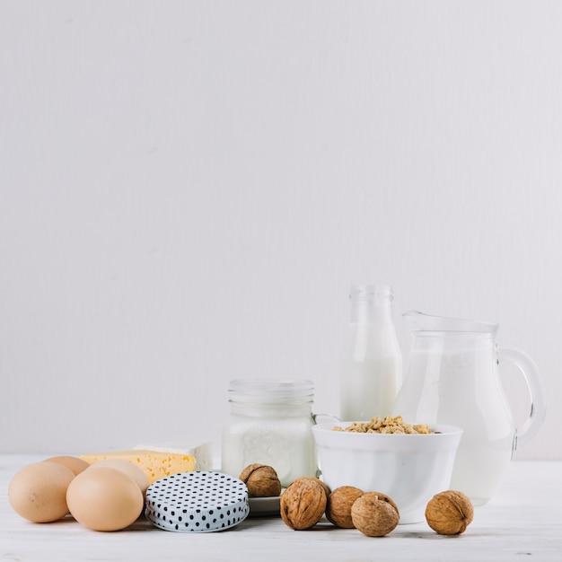 Milch; eier; schüssel mit getreide; käse und walnüsse auf weißem hintergrund Kostenlose Fotos