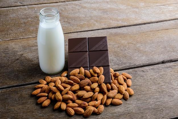 Milch in der flasche, in der schokolade und in der mandel auf hölzernem Premium Fotos