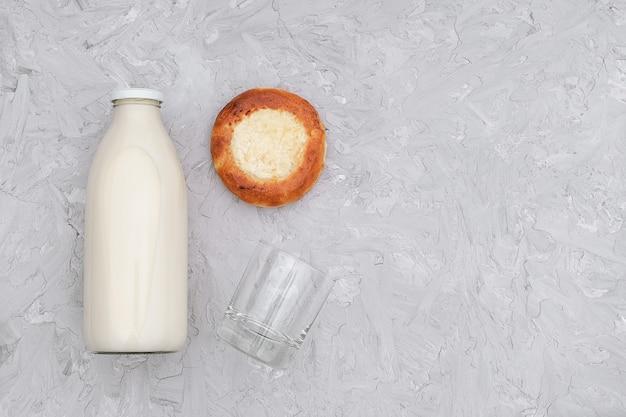 Milch in der glasflasche, in einem leeren glas und im frisch gebackenen brötchen auf grau Premium Fotos