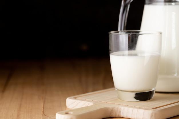 Milch in glas und krug auf holztisch Kostenlose Fotos