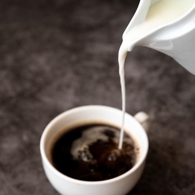 Milch in kaffeetasse gießen Kostenlose Fotos