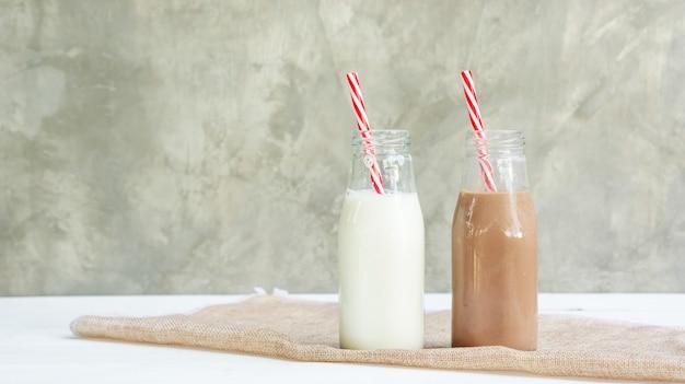 Milch- und schokoladenmilch auf einem weißen holztisch. Premium Fotos