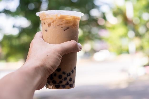 Milcheistee mit blase boba im plastikglas in der hand, neues getränk des taiwan-milcheistees Premium Fotos