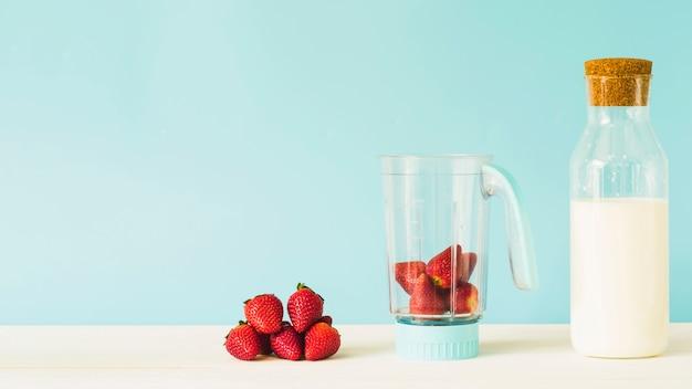 Milchflasche nahe erdbeere in der mischmaschine auf holztisch Kostenlose Fotos