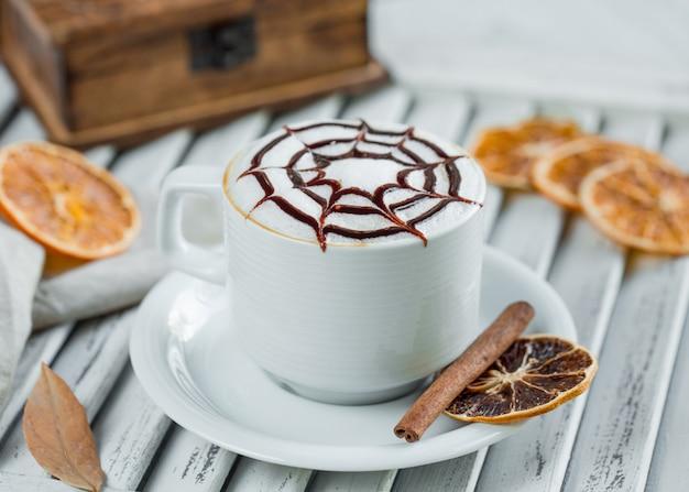 Milchiger cappuccino mit schokoladensirup in der weißen schale mit zimt- und orangenscheiben. Kostenlose Fotos
