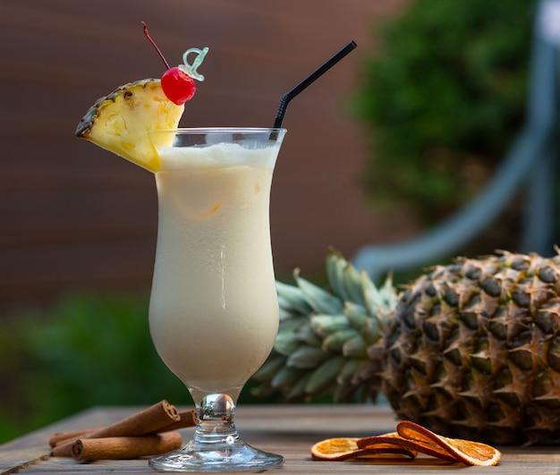 Milchiges cocktail im glas mit ananasscheibe und einer kirsche. Kostenlose Fotos