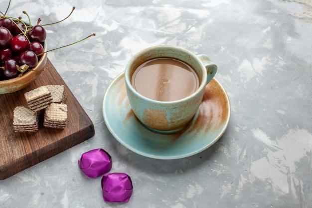 Milchkaffee mit bonbonwaffeln und sauerkirschen auf hellgrauem schreibtisch Kostenlose Fotos
