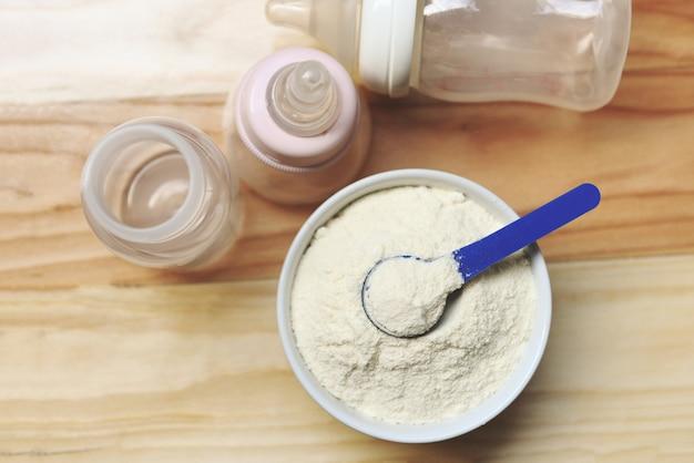 Milchpulver im löffel mit dosen- und babyflaschenmilch auf holztisch Premium Fotos