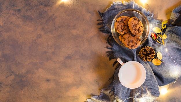 Milchschale mit keksen auf blauem plaid Kostenlose Fotos