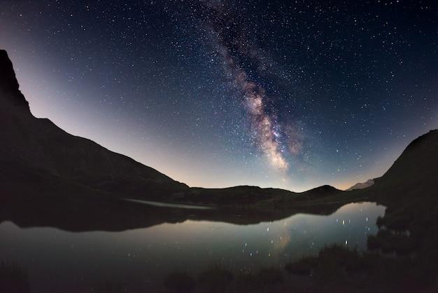 Milchstraße bogen und sternenhimmel spiegelt sich auf see in großer höhe auf den alpen. fisheye szenische verzerrung und 180-grad-ansicht. Premium Fotos