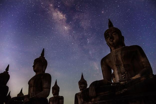 Milchstraßengalaxie mit dunkler filterart der buddha-statur Premium Fotos