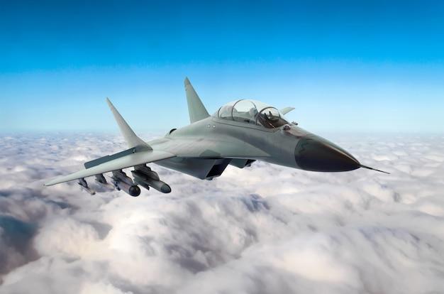 Militärischer kampfjet fliegt am himmel über den wolken Premium Fotos