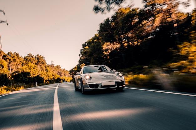 Mini-coupé unterwegs mit eingeschalteten scheinwerfern. Kostenlose Fotos