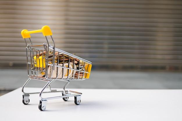 Mini-einkaufswagen enthalten stapelmünzen, die als e-commerce- und geschäftsmarketingkonzept verwendet werden Premium Fotos