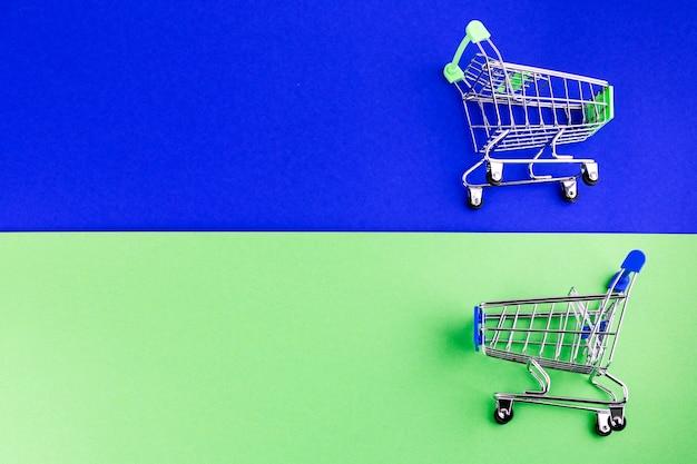 Mini-einkaufswagen zwei auf blauem und grünem doppelhintergrund Kostenlose Fotos