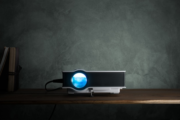 Mini führte projektor auf hölzerner tabelle in einem raumprojektorheimkinokonzept. Premium Fotos