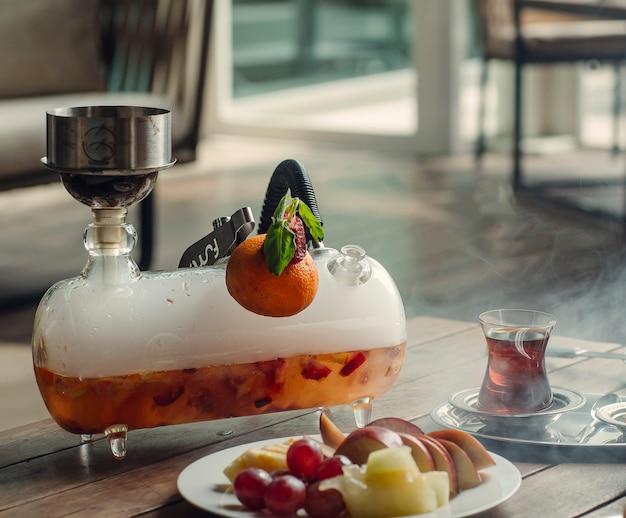 Mini glas shisha shisha mit erdbeer- und orangengeschmack beim tee-setup Kostenlose Fotos