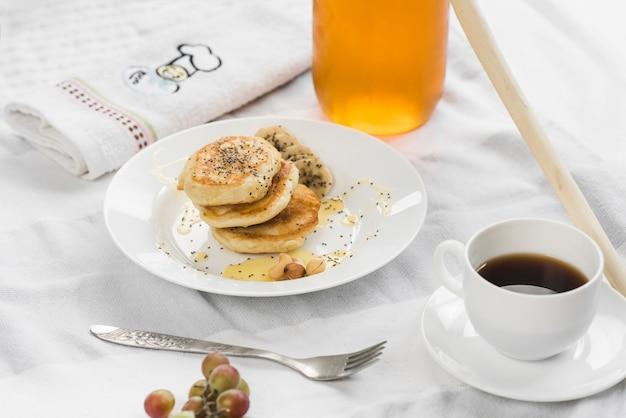 Mini-pfannkuchen mit banane; honig und chiasamen auf teller Kostenlose Fotos