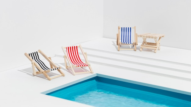 Miniatur-auswahl an sonnenliegen neben dem pool Kostenlose Fotos