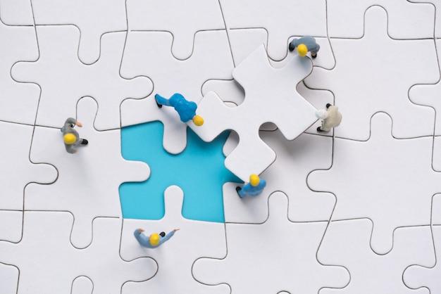 Miniatur-menschen-team versucht, das letzte puzzleteil zu vervollständigen Premium Fotos