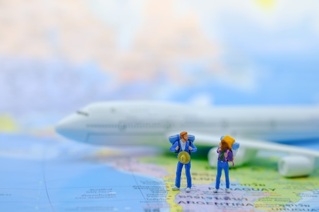 Miniaturfiguren des männlichen und weiblichen reisenden mit dem rucksack, der auf weltkarte mit flugzeugmodell steht. Premium Fotos