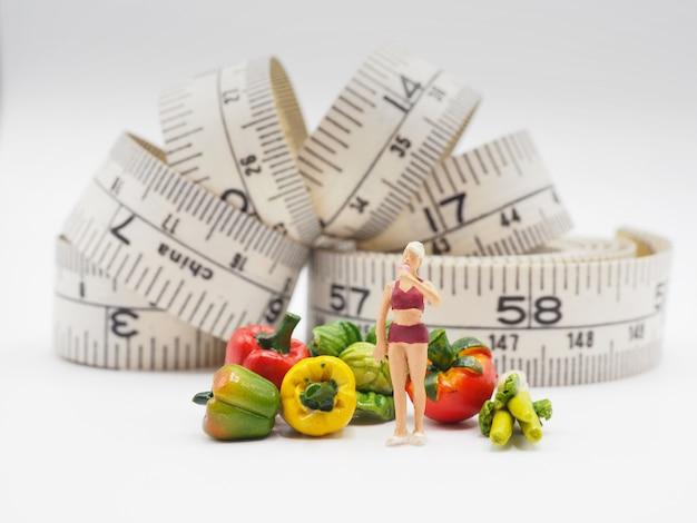 Miniaturfrau mit gemüse und messendem band auf weißem hintergrund, gesunder lebensstil Premium Fotos