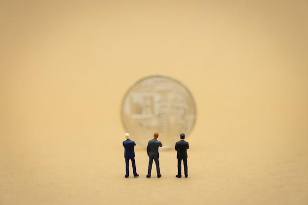 Miniaturgeschäftsmänner mit 3 leuten, die mit der rückseite verhandelt im geschäft stehen. Premium Fotos