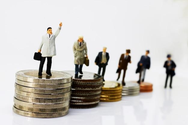 Miniaturgeschäftsmann, der auf schritt des münzengeldes geht Premium Fotos