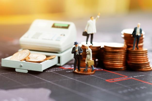 Miniaturgeschäftsmann mit münzenstapel. Premium Fotos