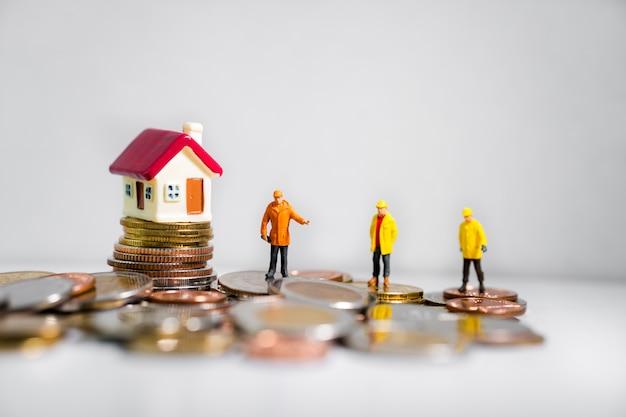Miniaturingenieure, die mit minihaus auf stapelmünzen stehen Premium Fotos