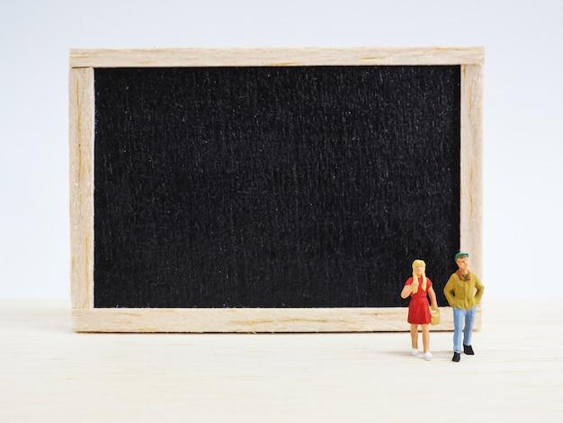 Miniaturkinder, die vor einer tafel auf hölzernem hintergrund stehen. zurück zum schulkonzept. Premium Fotos