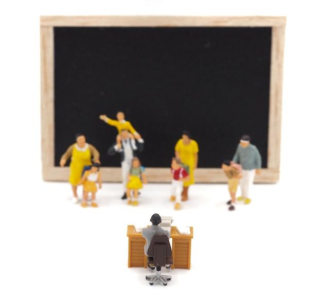 Miniaturkinder, die vor einer tafel auf weißem hintergrund stehen. zurück zum schulkonzept. Premium Fotos