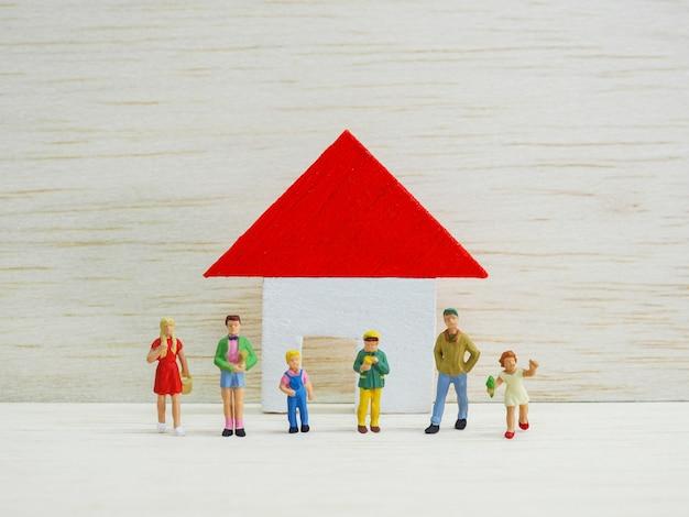 Miniaturkinder, die vor kleinem haus auf hölzernem hintergrund stehen. zurück zum schulkonzept. Premium Fotos
