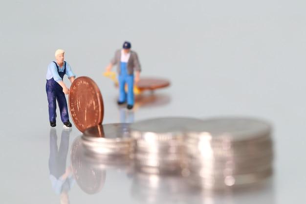 Miniaturleute: arbeitskraft mit münzen, geschäftskonzept unter verwendung als hintergrund Premium Fotos