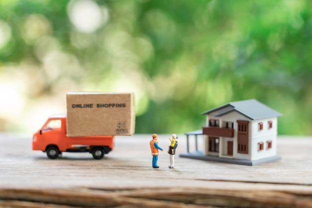 Miniaturleute bauarbeiter online-shopping mit einkaufswagen und shopping Premium Fotos