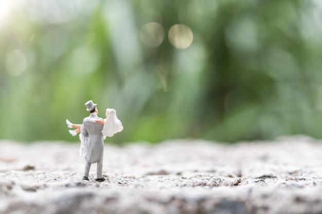 Miniaturleute: braut- und bräutigampaare, die im freien stehen Premium Fotos