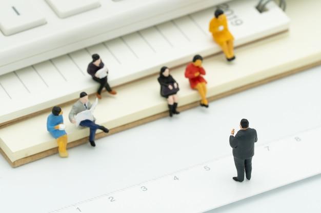 Miniaturleute, die auf anmerkungsbuch sitzen, setzten weißen hintergrund ein. besprechung oder diskussion Premium Fotos