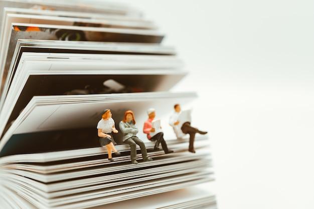 Miniaturleute, die auf dem papier verwenden als bildung und soziales sitzen Premium Fotos