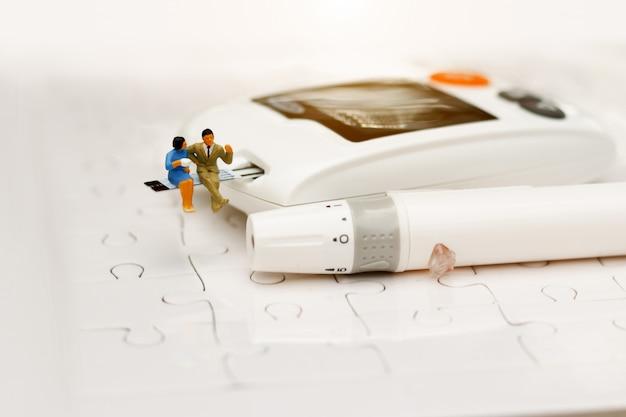 Miniaturleute, die auf einem glukosemeter von diabetes, gesundheitswesenkonzept sitzen. Premium Fotos