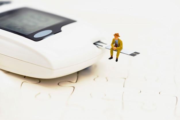 Miniaturleute, die auf einem glukosemeter von diabetes sitzen Premium Fotos
