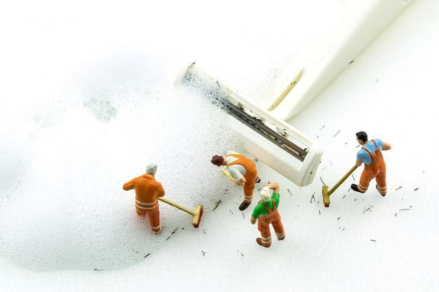 Miniaturleute, die schmutzigen weißen rasierapparat auf weißem hintergrund säubern. Premium Fotos