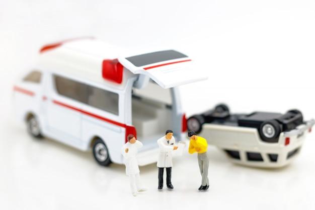 Miniaturleute: doktor und patient, die mit krankenwagen stehen. Premium Fotos