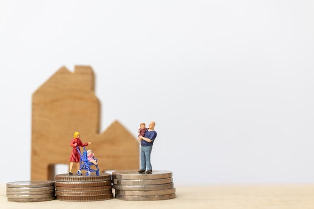 Miniaturleute: eltern mit kindern mit dem haus und münzen-stapeln Premium Fotos