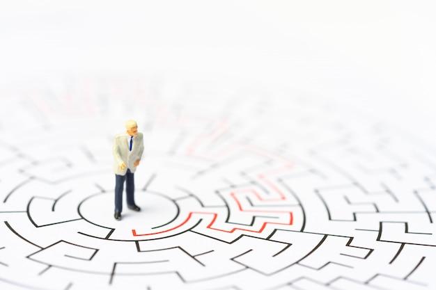 Miniaturleute, geschäftsmann im labyrinth oder labyrinth, die den ausweg herausfinden. Premium Fotos