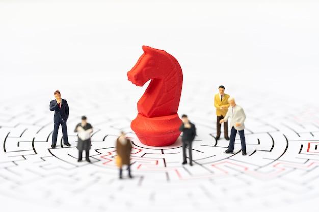 Miniaturleute, geschäftsmann und schachfiguren im labyrinth oder im labyrinth, die den ausweg herausfinden. Premium Fotos