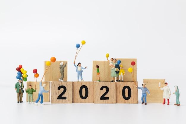 Miniaturleute: glückliche familie, die ballon auf holzklotz nr. 2020 hält Premium Fotos