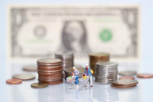 Miniaturleute: käufer, der neben geld, geschäft unter verwendung als hintergrund geht Premium Fotos