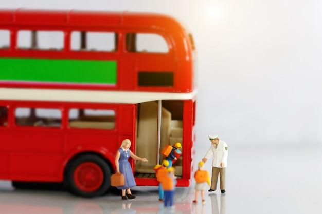 Miniaturleute, kinder, die mit dem lehrer in den schulbus steigen. Premium Fotos
