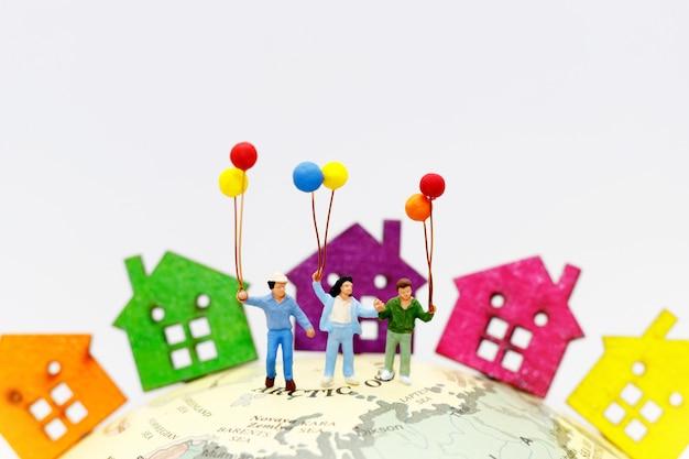 Miniaturleute mit der familie, die ballon mit häusern auf der kugel hält. Premium Fotos