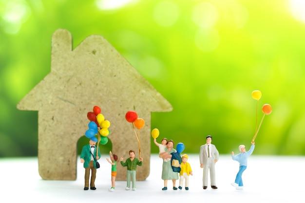 Miniaturleute mit der familie, die ballon mit haus hält. Premium Fotos